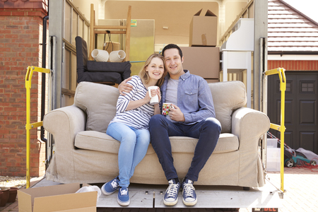 removal van: Couple With Sofa On Tail Lift Of Removal Truck Moving Home