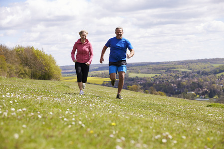 Mature Couple Jogging In Countryside Stock Photo