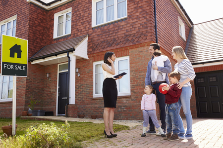 family outside: Realtor Outside House For Sale With Young Family