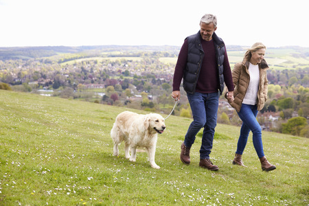 Mature Couple Taking Golden Retriever For Walk Reklamní fotografie - 71235796