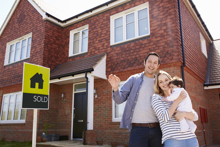 Portrait Of Young Family With Keys To New Home