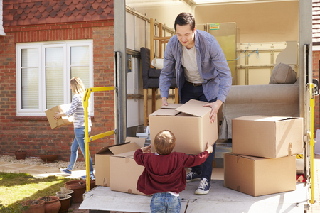 removal van: Family Unpacking Moving In Boxes From Removal Truck Stock Photo