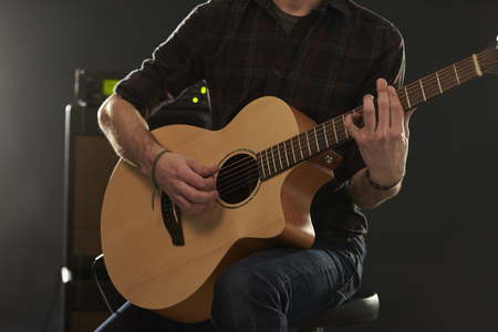 amplified: Close Up Of Man Playing Amplified Acoustic Guitar