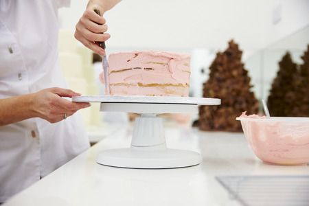 Close Up Of Woman In Bakery Decorating Cake With Icing Imagens