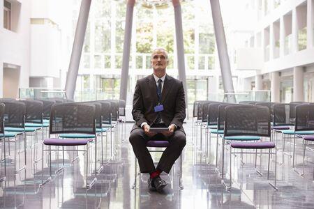 keynote: Businessman In Empty Auditorium Preparing To Make Speech