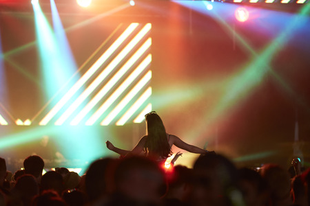 night out: Woman Sitting On Friends Shoulders At Music Festival Stock Photo