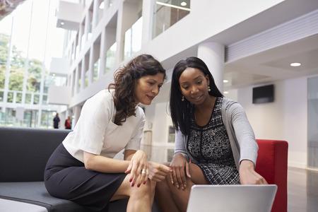 personas trabajando en oficina: Dos Empresarias que usan la computadora portátil en pasillo de la oficina moderna