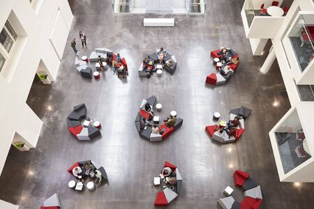 view of an atrium in a building: Student groups on seating in a modern university atrium