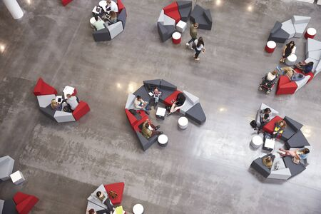 view of an atrium in a building: Students groups sitting in a modern university atrium Stock Photo