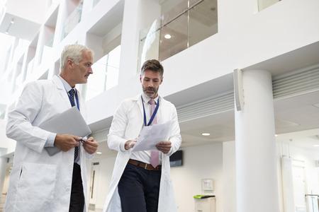 Deux médecins parlent comme ils traversent l'hôpital moderne