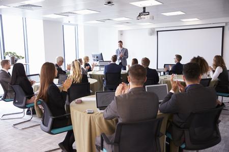 delegates: Delegates Applauding Businessman Making Presentation