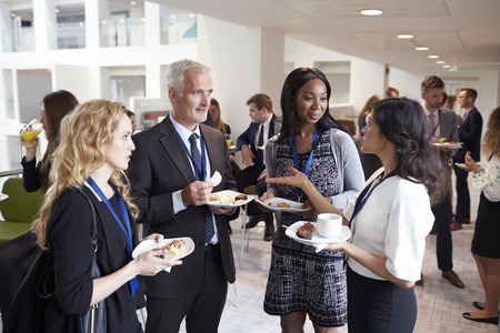 Delegates Networking During Conference Lunch Break Stock Photo