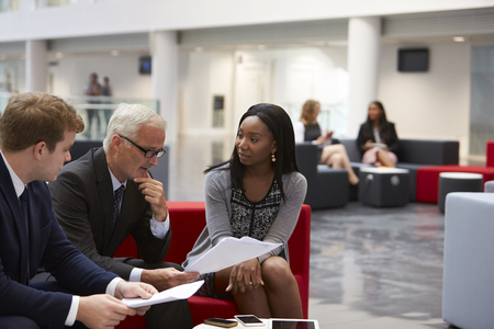 Businesspeople Discuss Document In Lobby Of Modern Office