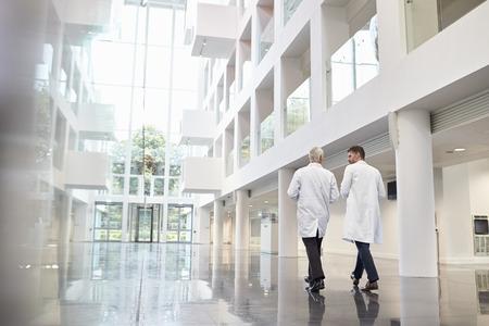 Achteraanzicht van artsen die praten als ze door het ziekenhuis lopen