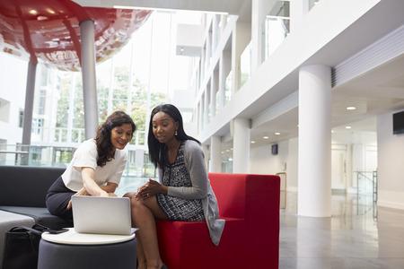 Two Businesswomen Using Laptop In Lobby Of Modern Office Stock Photo