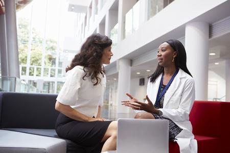 Doctor And Patient Having Meeting In Hospital Reception Area 版權商用圖片