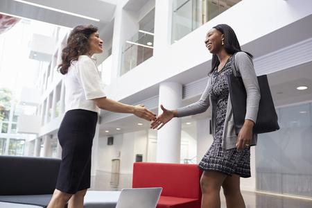 近代的なオフィスのロビーで握手する 2 人のビジネスウーマン 写真素材
