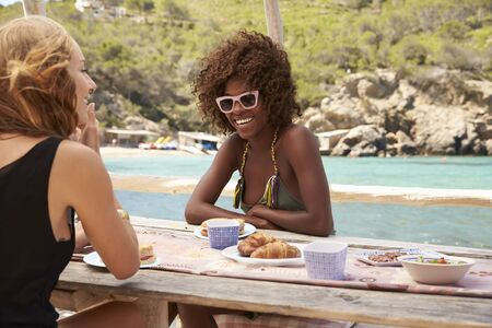 getting out: Two female friends talking over food at a table by the sea Stock Photo