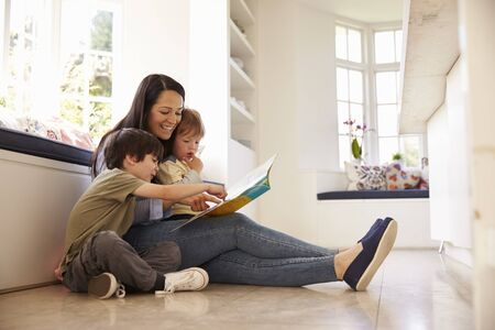 18 30s: Mother And Sons Reading Story At Home Together Stock Photo