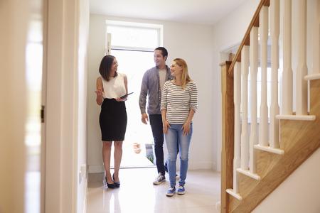 Mostrando agente de bienes raíces Pareja joven alrededor de la propiedad para venta
