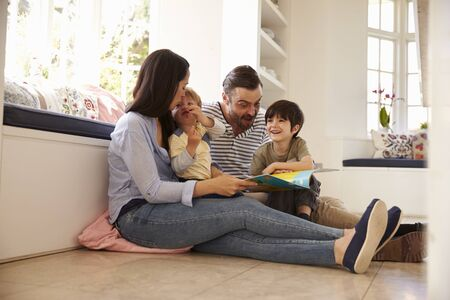 18 30s: Family Sitting On Floor Reading Story At Home Together Stock Photo