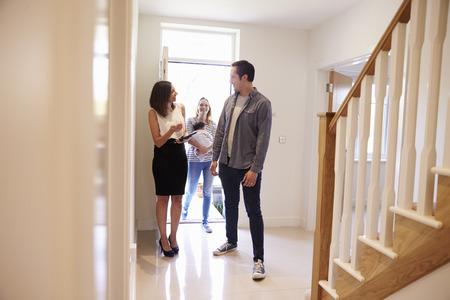 race for time: Realtor Showing Young Family Around Property For Sale