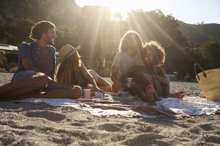 Due coppie che hanno un picnic sulla spiaggia, lens flare, Ibiza