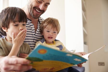 three months old: Close Up Of Father And Sons Reading Story At Home Together