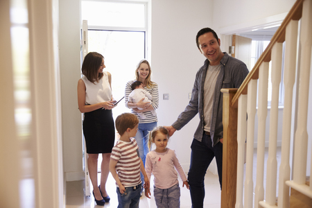 Realtor Showing Young Family Around Property For Sale Imagens - 71259286