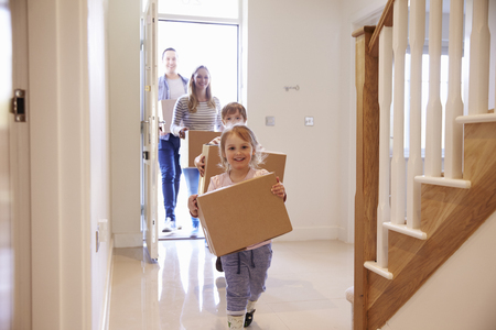 Family Carrying Boxes Into New Home On Moving Day Foto de archivo