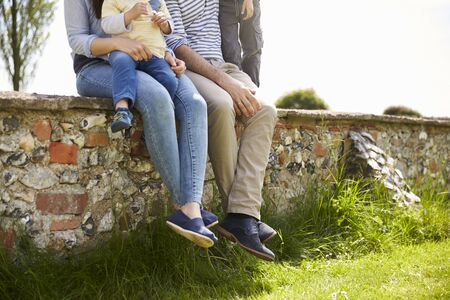 18 30s: Family Sitting On Wall During Walk In Summer Countryside
