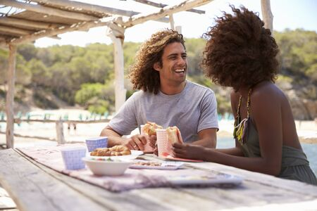 Young couple eating at a table by the sea look at each other
