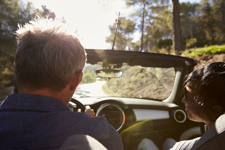 Couple driving in open top car, rear passenger point of view Stock Photo