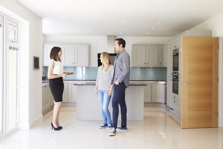 Zeigte Immobilienmakler Junge Paar Around Zu verkaufen