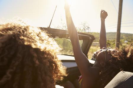 Pareja joven en un coche descapotable, mujer con los brazos levantados Foto de archivo