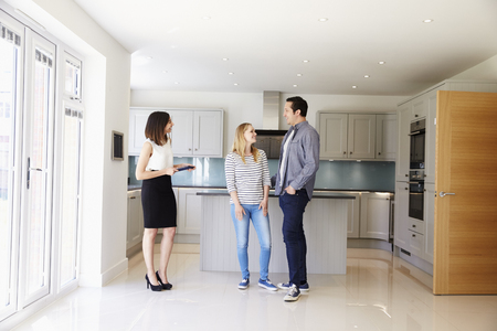 property: Realtor Showing Young Couple Around Property For Sale