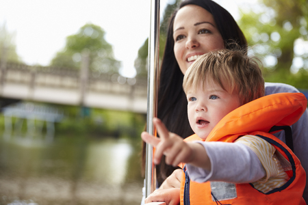 lifejacket: Mother And Son Enjoying Day Out In Boat On River Together