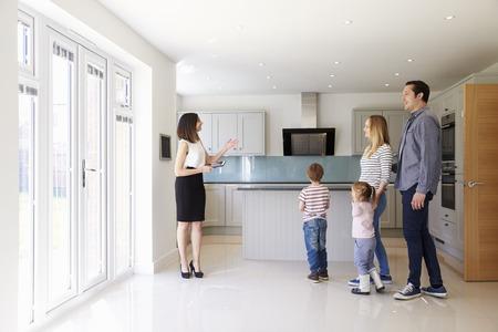 Realtor Mostrando Família nova em torno da propriedade Venda Imagens