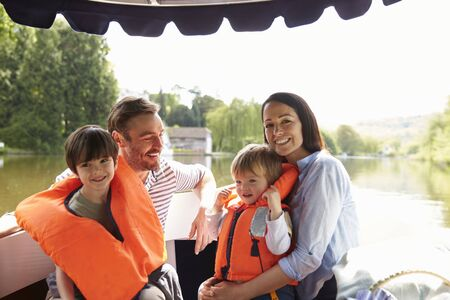 18 30s: Family Enjoying Day Out In Boat On River Together