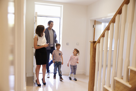 viewing: Realtor Showing Young Family Around Property For Sale