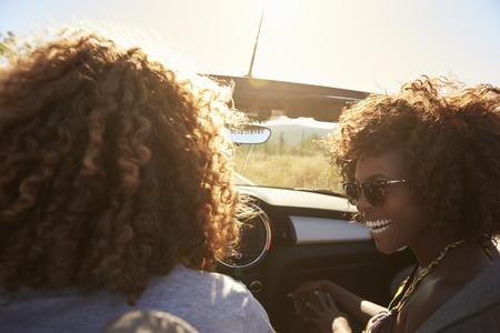 Paar in een open top auto, achter passagiers oogpunt
