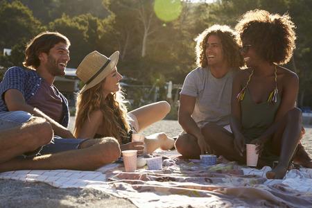 Twee paren met een picknick op het strand, backlit, close-up