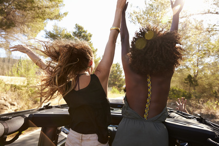 Two excited women stand in the back of open car, back view Stock Photo - 71304753