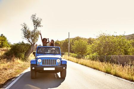 Vier vrienden op de weg in open auto, twee vrouwen staan Stockfoto