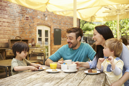 18 30s: Family Sitting At Outdoor Cafe Table Having Lunch Stock Photo