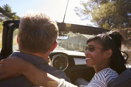 man close up: Couple driving, woman looking at man, close up back view