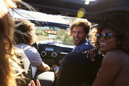 Four friends driving in an open top car, rear passenger POV Stock Photo