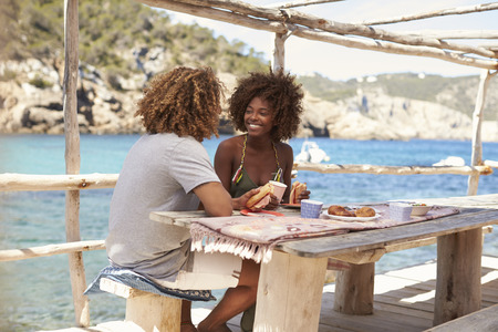 getting out: Mixed race couple having a meal by the sea, vertical, Ibiza