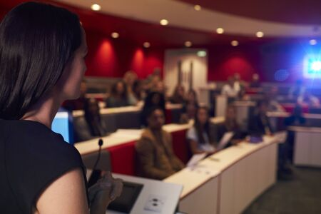 lecturing: Woman lecturing students in lecture theatre, focus foreground