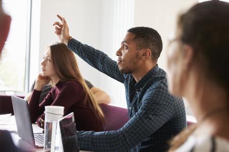 캠퍼스에서 강의에 참석하는 동안 질문하는 학생